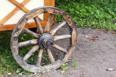 Ancient wooden wheel of cart. Wood dray on ground with green grass. Inventing wheel illustration