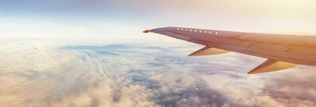 コピースペース付きのフライトウィングパノラマ。地球と雲の上の航空機の翼。空の飛行。休暇のための航空会社による旅行。