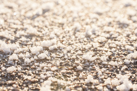 Frozen ground surface texture close up. Big snowflakes background