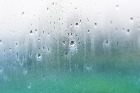 Water drops on misted glass with green and blue background.
