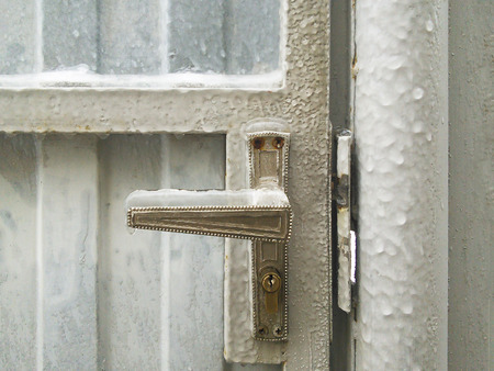 Frozen and ice covered door handle. Very cold winter weather