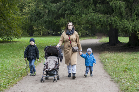 Family of mother and two boys walk in park with empty stroller