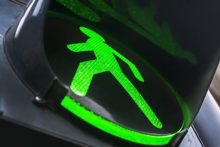 Green traffic light for pedestrians. Footers in cities allowed to walk