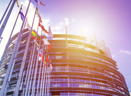 EU Parliament building with flags in sun light. Background for European news