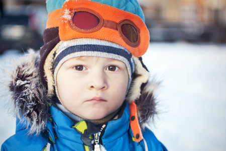 Toddler in snow winter in fur coat and pilot hat. Cold for kids 스톡 콘텐츠