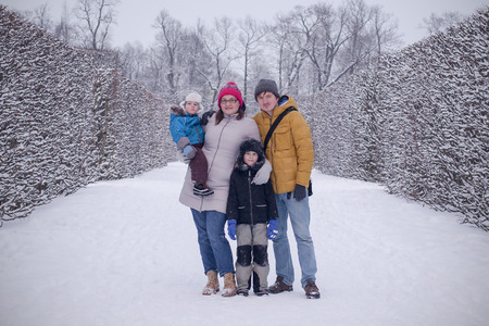Happy family in cold winter park staying together. Fou people: husband and wife with two kids