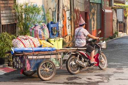Asian man on bike with colorful cargo in the cart