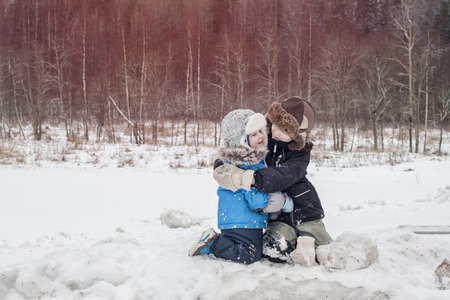 Two happy toddler boys embrace during the play. Kid's friendship in winter snowy forest 스톡 콘텐츠