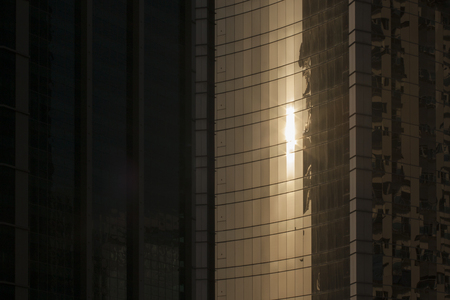Sun reflects on skyscraper's window close up. Megapolis sunset atmosphere. 스톡 콘텐츠