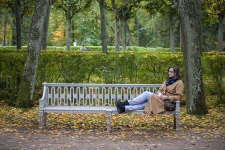 Woman relaxes sitting on a bench in autumn park. Yellow leaves around.