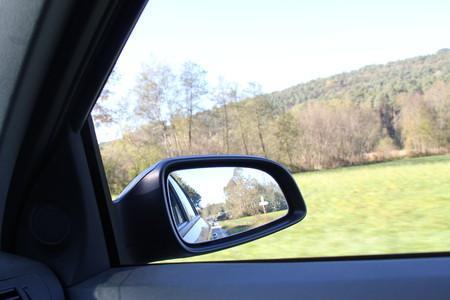 retrovisor: Espejo retrovisor del coche y en el camino. Foto de archivo