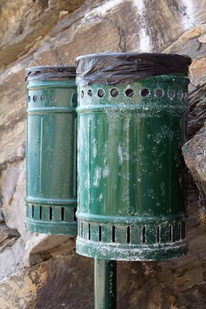 rejections: Pair of bins for waste, metal, green color. In the background the rock. Stock Photo