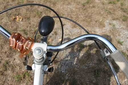 footrest: Detail of the handlebar of a bicycle for women. Complete with chain and padlock, footrest for children.