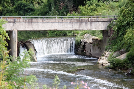 induced: Little waterfall in the river Olona, Lombardy northern Italy, old industrial area.