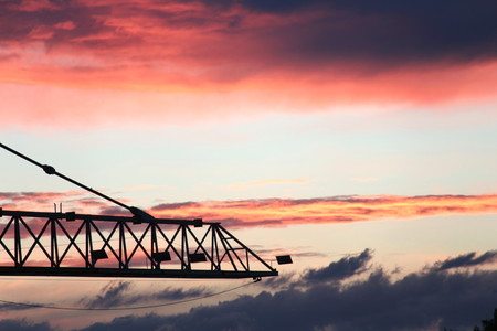 economic recovery: The crane for the building, clouds on the background of red color.Concept of economic recovery in the building - red sky at night time hopefully -.