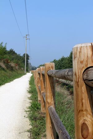 Dirt road for bike, in the summer. With parapet side built of wood.