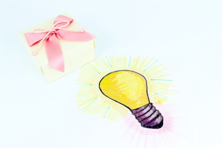 A stylised illustration of a light bulb that has been sketched on a sheet of paper. Idea of a gift with floral decorations.