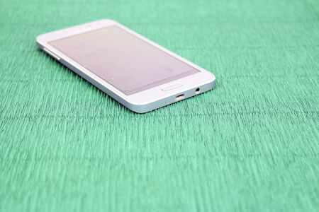 Smartphone on green paper background Standard-Bild