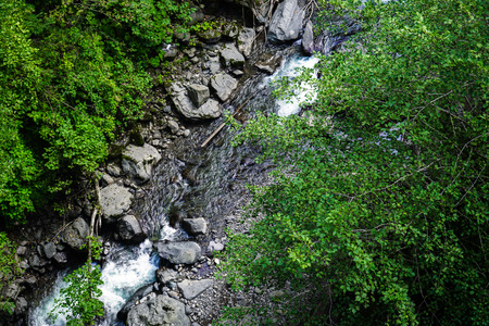 Mountain River rages on rocks on a sunny day