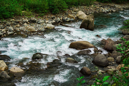 Mountain River rages on rocks on a cloudy day Stock Photo