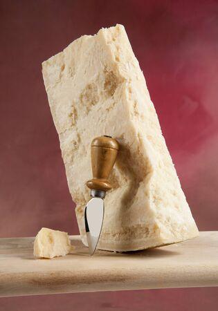 boxcutter: Parmigiano Reggiano cheese piece with boxcutter Stock Photo