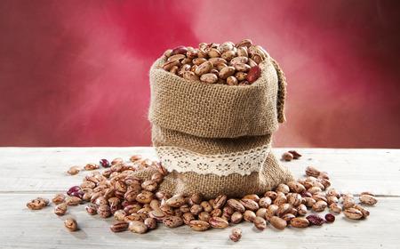jute sack: borlotti beans in jute sack on white wooden table