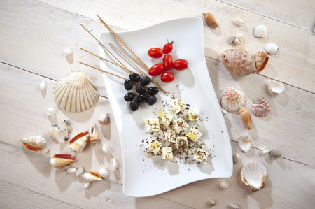 nibbles: Mediterranean appetizer with Greek feta with shells around Stock Photo