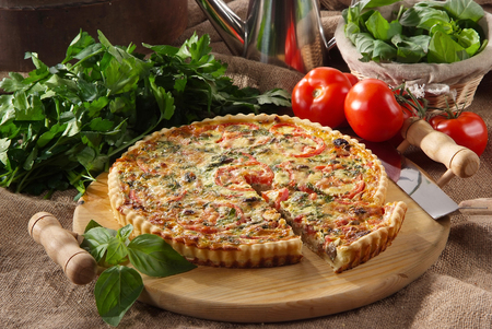 Mediterranean savory pie on rustic wooden cutting board with vegetables