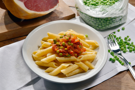 pastasciutta: Penne with ham gravy and peas on a wooden table
