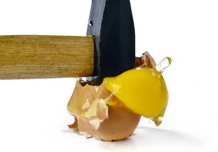 Broken egg with a hammer on a white background