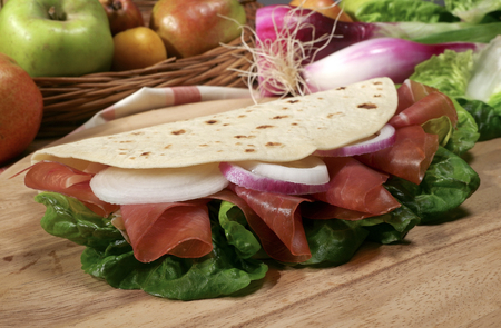 Piadina Italiana with ham, salad, onion, on a wooden cutting board