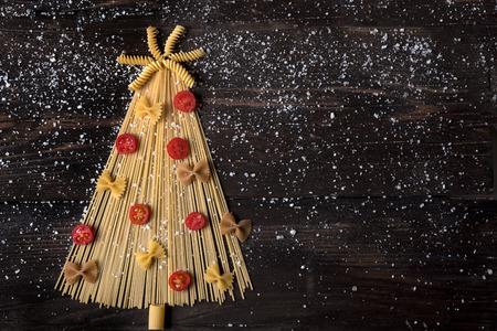 Kerstboom gemaakt met Italiaanse spaghetti op een houten tafel met zout