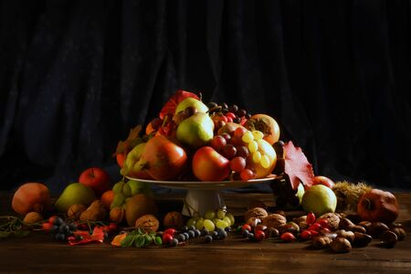Fruits of autumn still life on a plate with setting, on to a wooden table Stock Photo