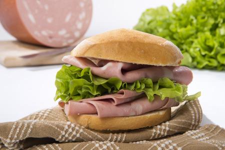 Mortadella sandwich on a napkin, on the entire mortadella background Stock Photo - 90873830