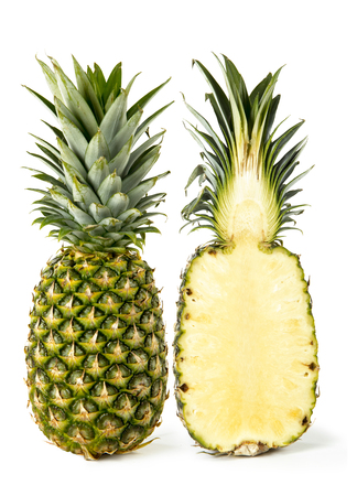 A whole pineapple and a pineapple cut in half on a white background
