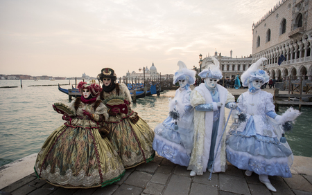 Masked figures posing during the carnival in Venice