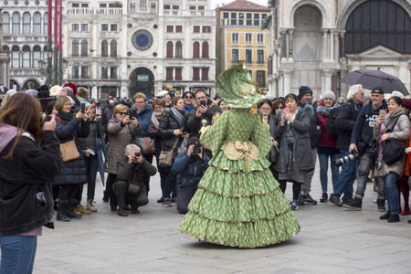 Tourists in Venice photographing a masked woman for Carnival