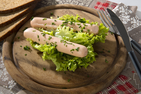 Bavarian wurstel served with chives on a wooden chopping board