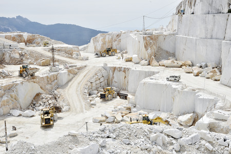 Bulldozers at work in a quarry of white marble