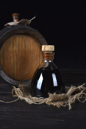 Balsamic vinegar of Modena on a jute canvas and with barrel behind