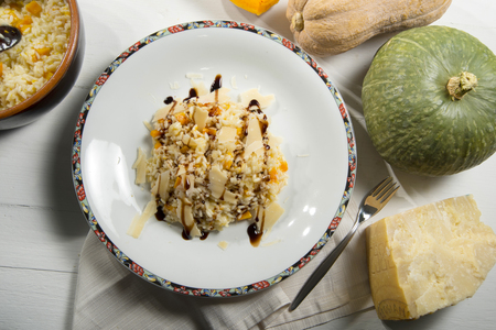 Pumpkin rice with balsamic vinegar and parmesan in a decorated plate