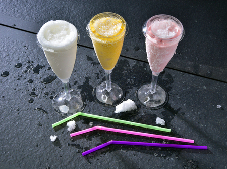 Sorbets cold ice cream with straws on a black table Stock Photo - 117544552