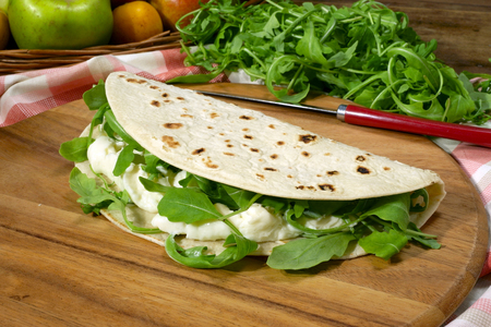 Piadina Romagnola stuffed with stracchino and rocket on a wooden cutting board Stock Photo