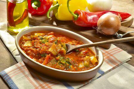 peperoni cotti con pomodori e cipolle affettate.