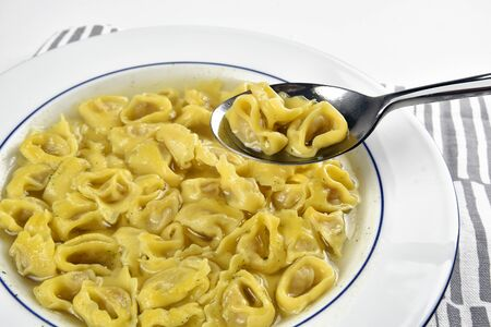 Dish with tortellini in broth and a spoon with some tortellini