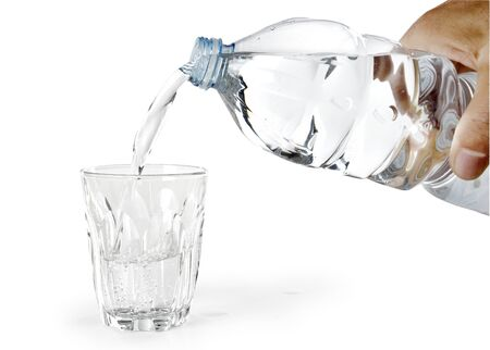 Fill a glass of water with a bottle on a white background