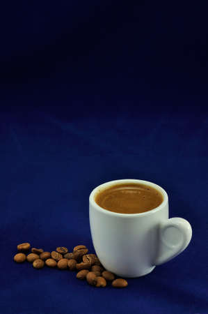 a cup of turkish , greek coffee and fresh roasted coffee beans on a dark blue  surface  photo