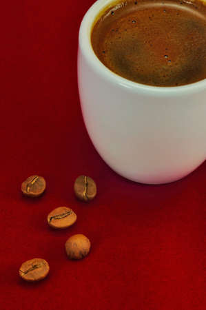 a cup of turkish , greek coffee and fresh roasted coffee beans on a red surface  photo