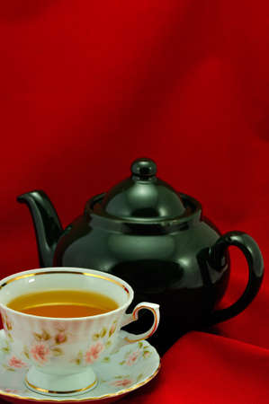 A cup of tea and green teapot on a red background photo