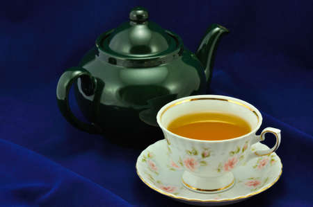 A cup of tea and green teapot on a blue background photo